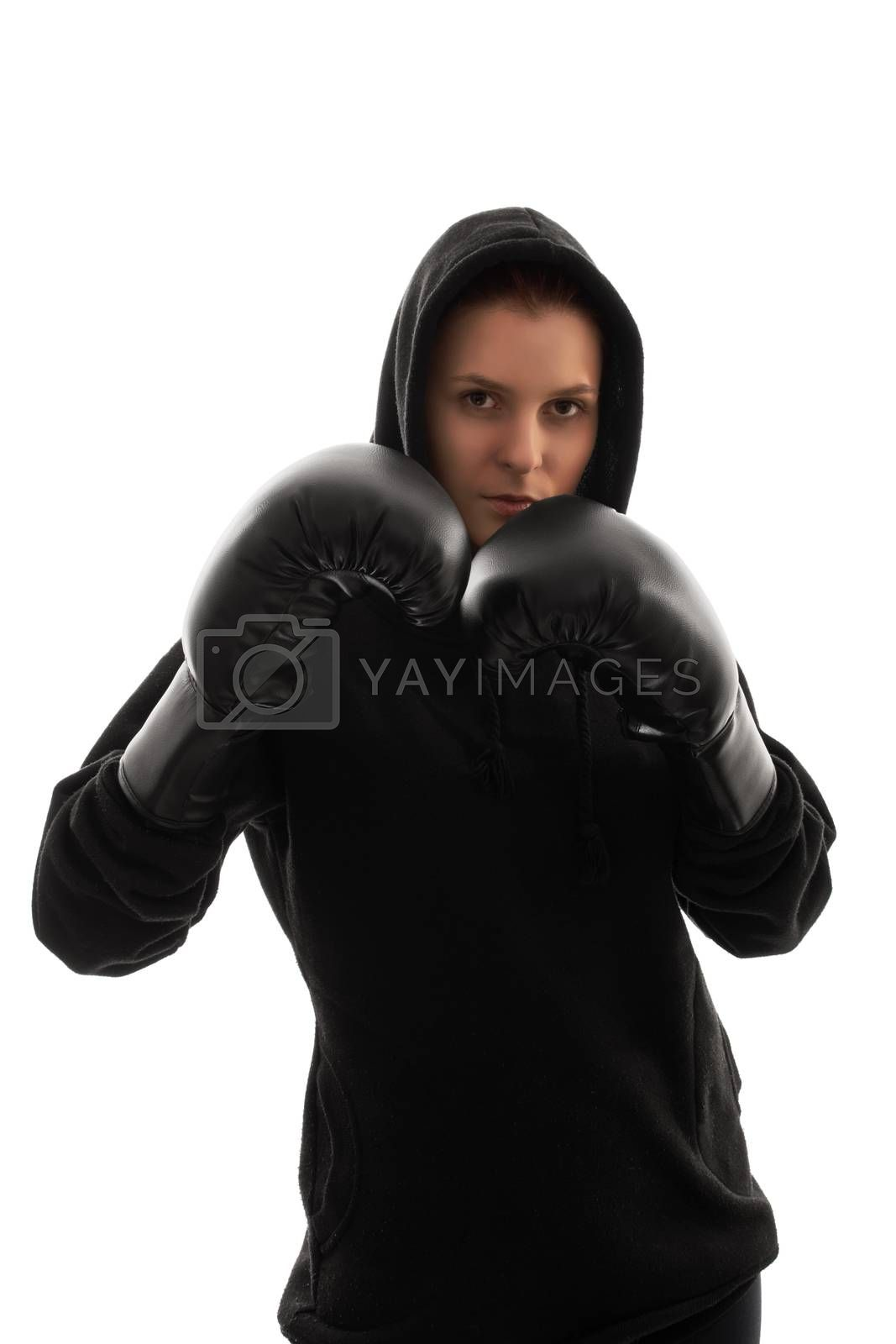 A portrait of a beautiful young girl with boxing gloves holding her guard up, with harsh lightning, isolated on white background.
