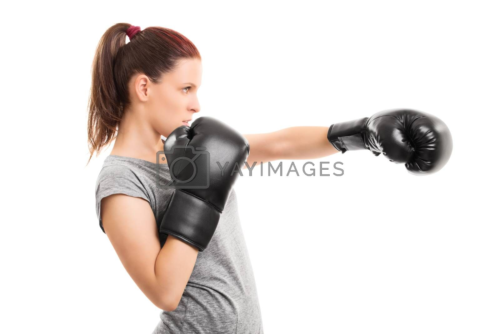 Profile shot of a beautiful young girl with boxing gloves punching, isolated on white background.
