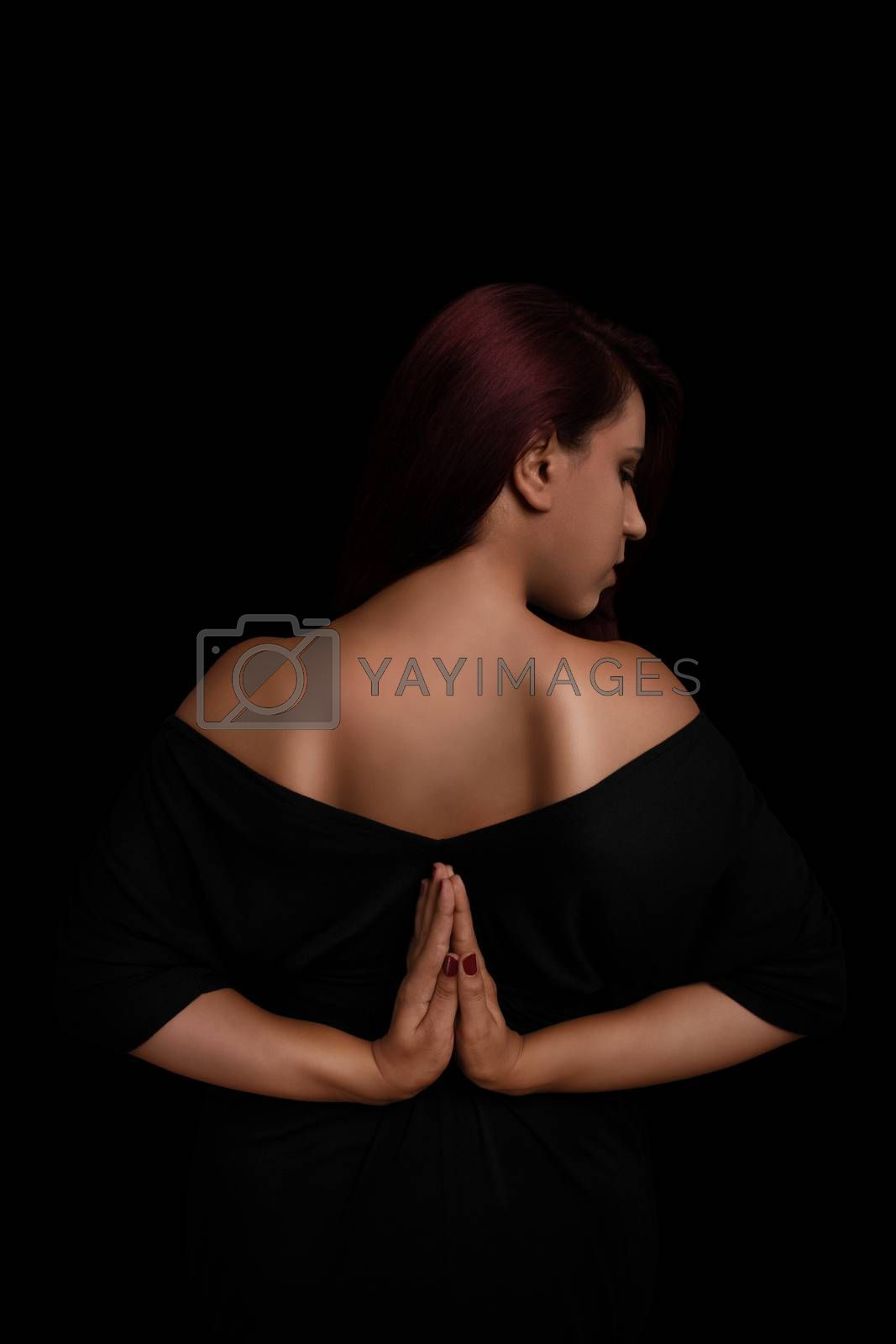 Low key portrait of a young girl in black dress with her hands behind her back, practicing yoga isolated on black background.