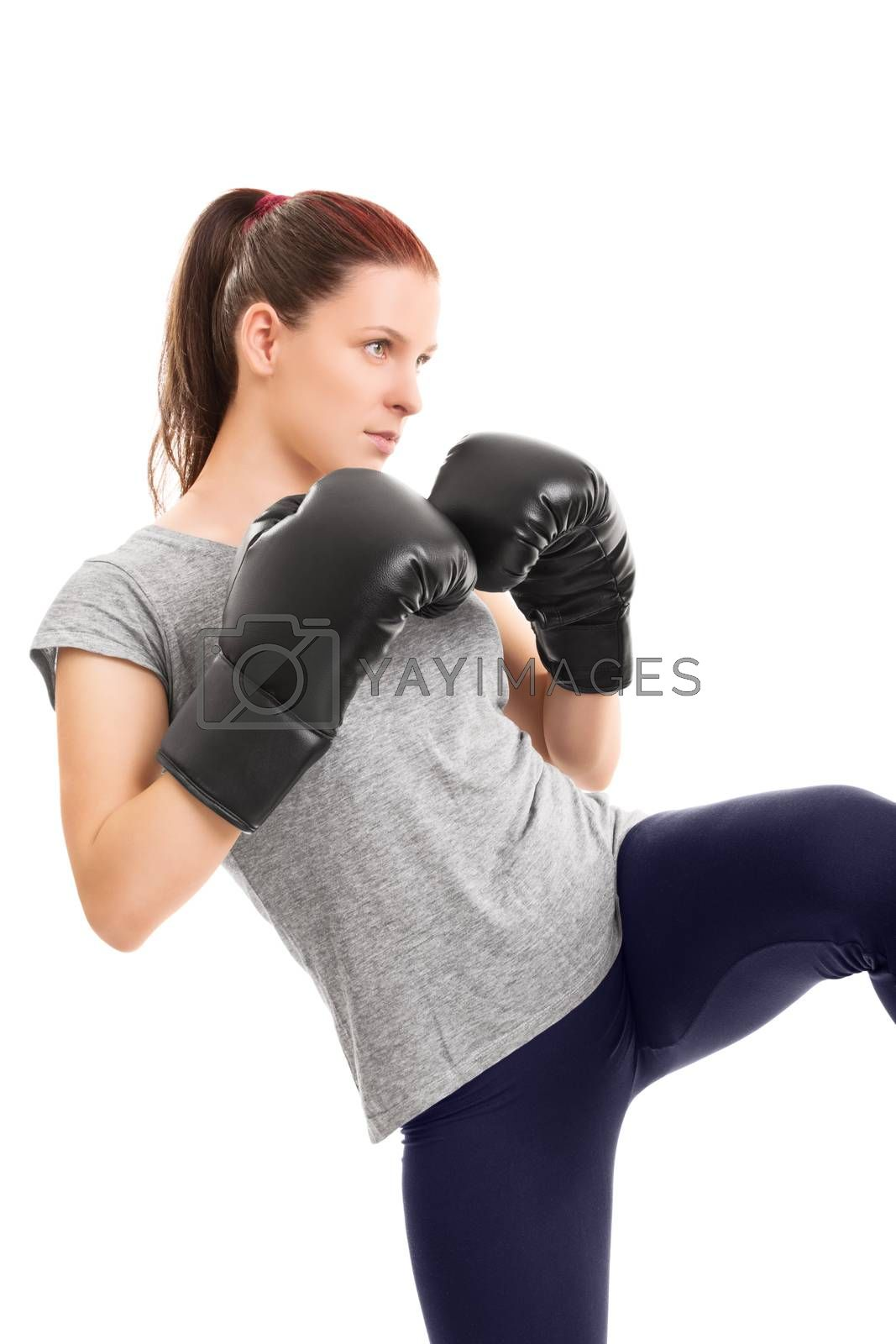 A profile of a beautiful young girl with boxing gloves delivering a kick, isolated on white background.