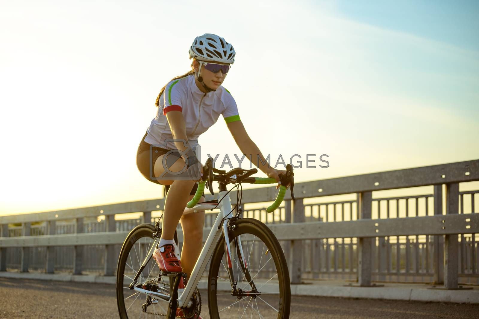 Young Woman Cyclist Riding Road Bicycle on the Street in the City at Hot Summer Sunset. Healthy Lifestyle and Urban Sport Concept.