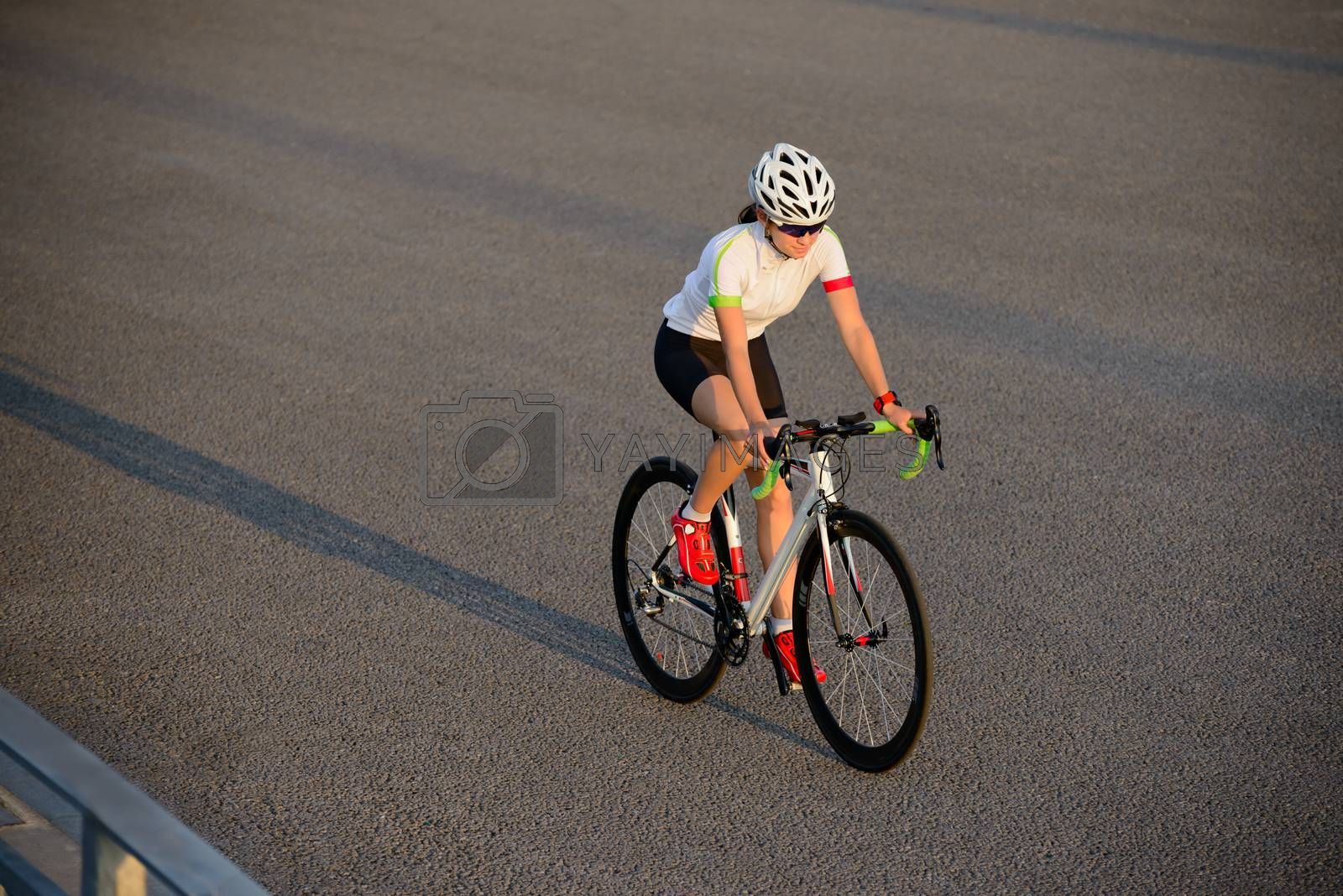 Royalty free image of Young Woman Riding Road Bicycle on Free Street in the City at Sunset. Healthy Lifestyle and Sport Concept. by maxpro