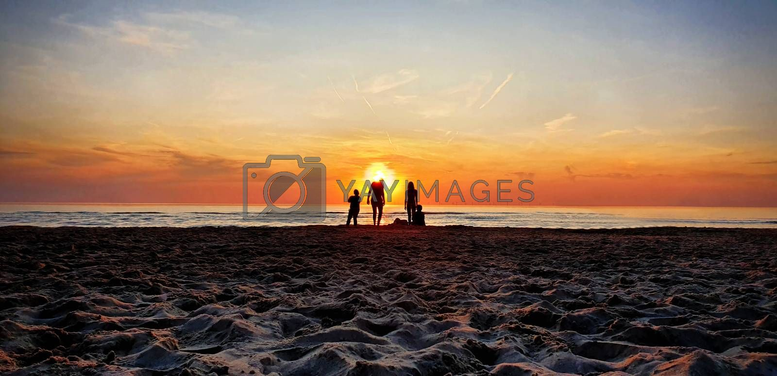 Silhouettes of people at a sandy beach enjoying the golden hour, watching the sunset.