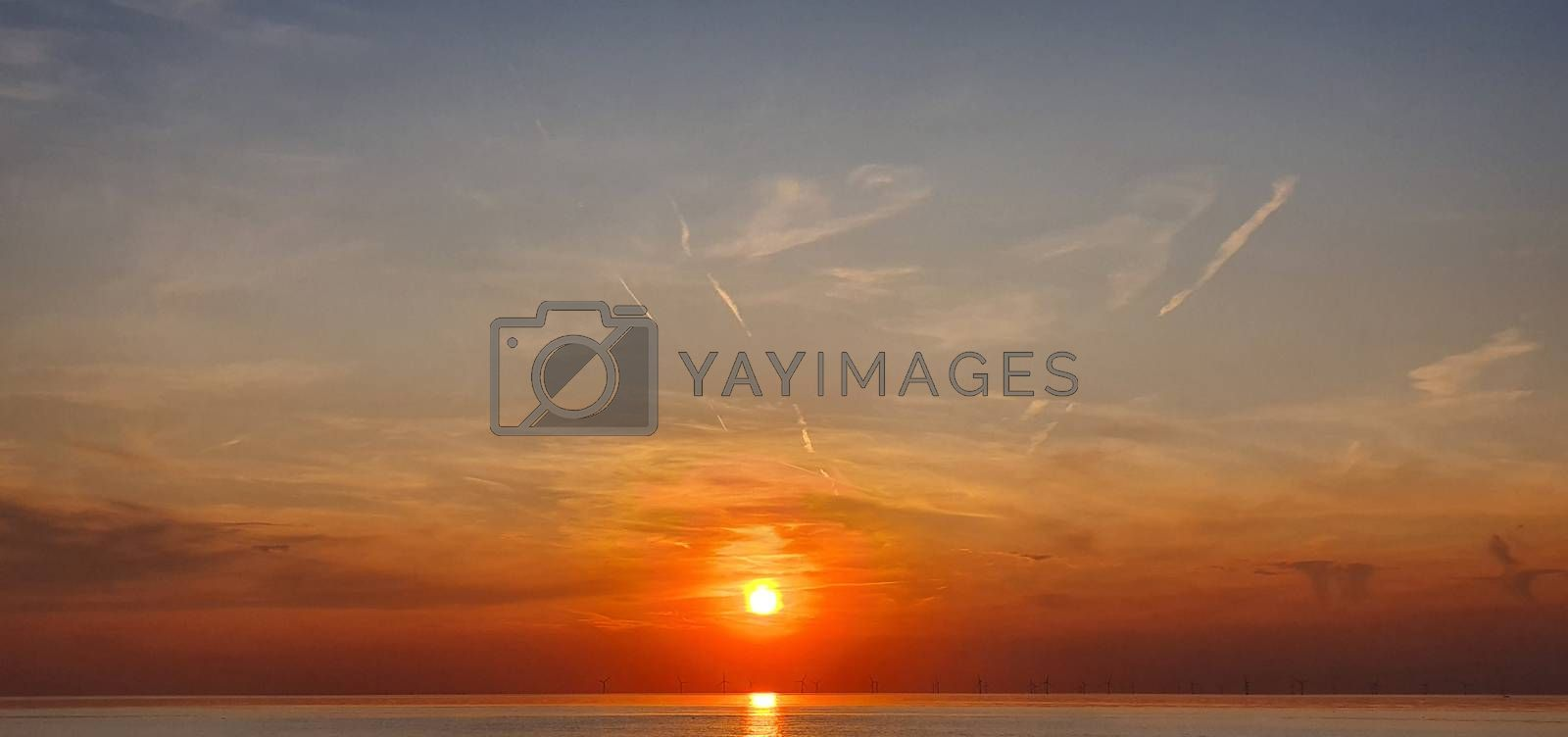 Windmills in the North Sea during fiery orange sunset.