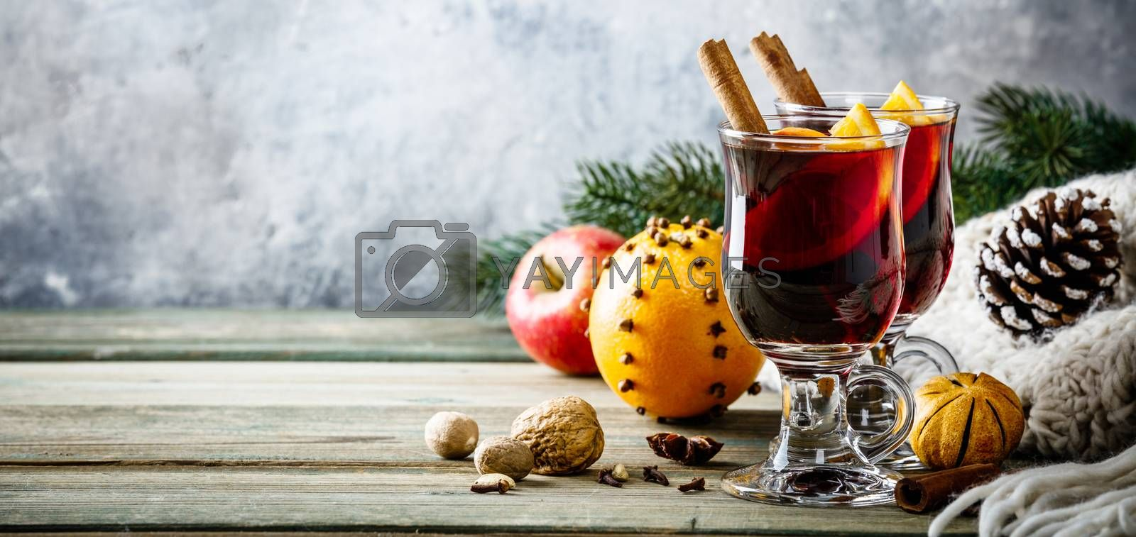 Mulled wine with spices and orange slices on wooden table