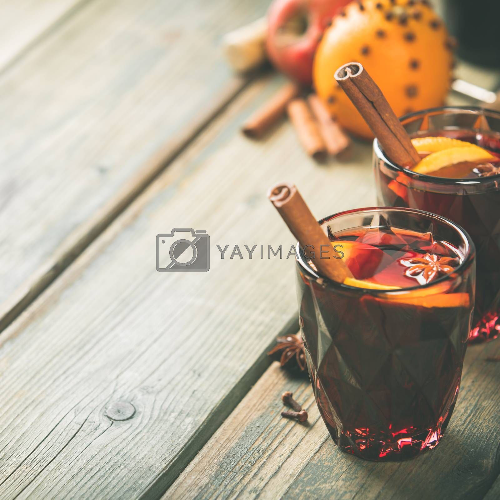 Mulled wine with spices and orange slices on wooden table. Space for text