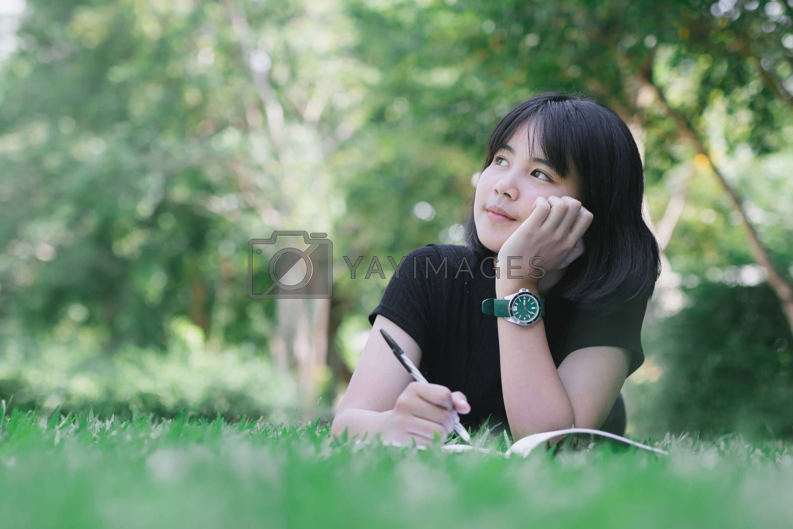 The girl is sitting in the lawn in the garden. by aekgasit