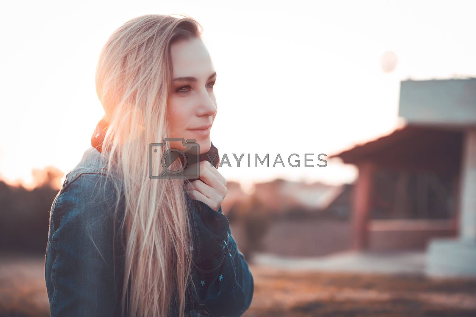 Fashion woman portrait, beautiful blond girl outdoors in sunset light, autumn style, urban life of young people