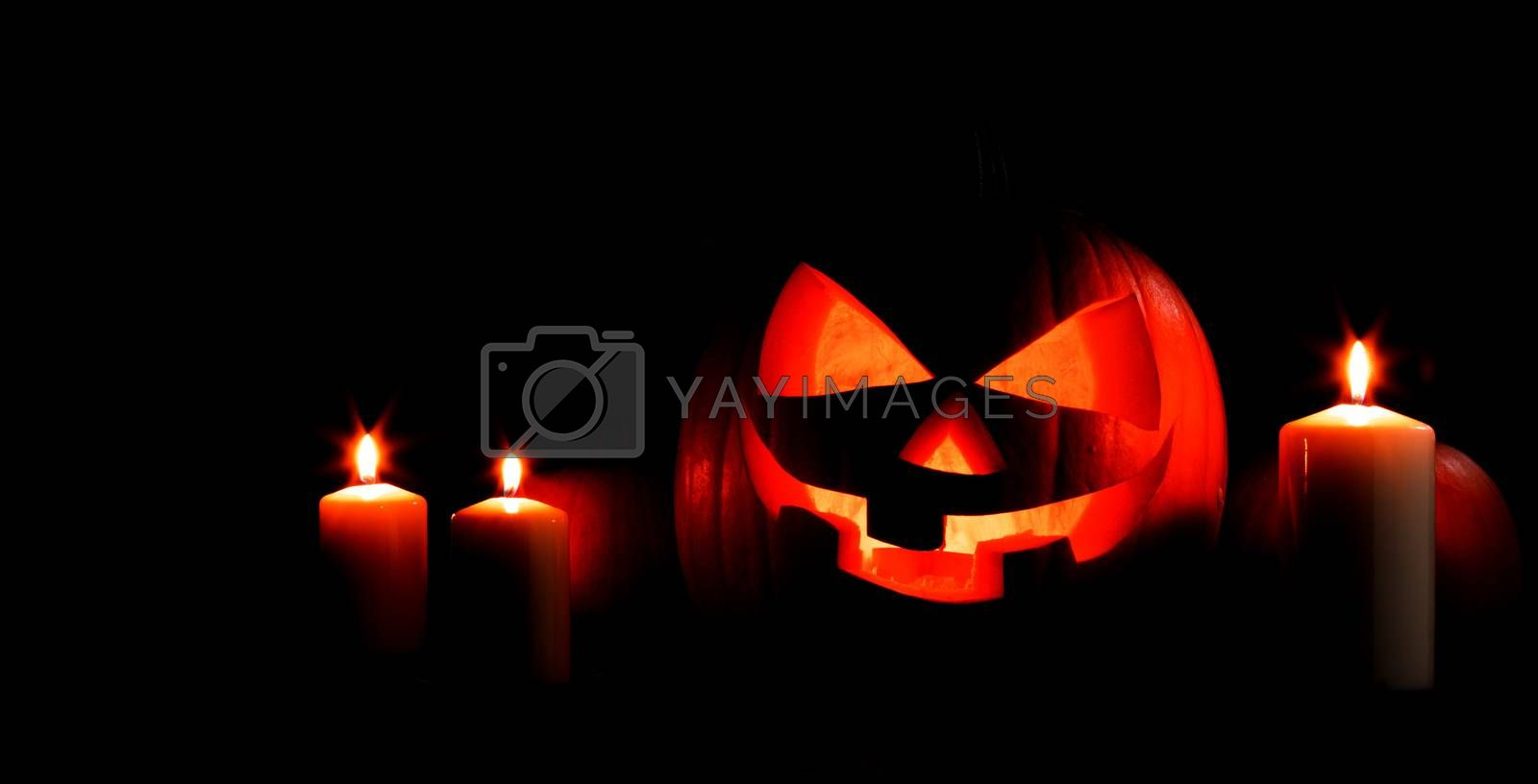 Halloween pumpkin head jack lantern and candles on black background