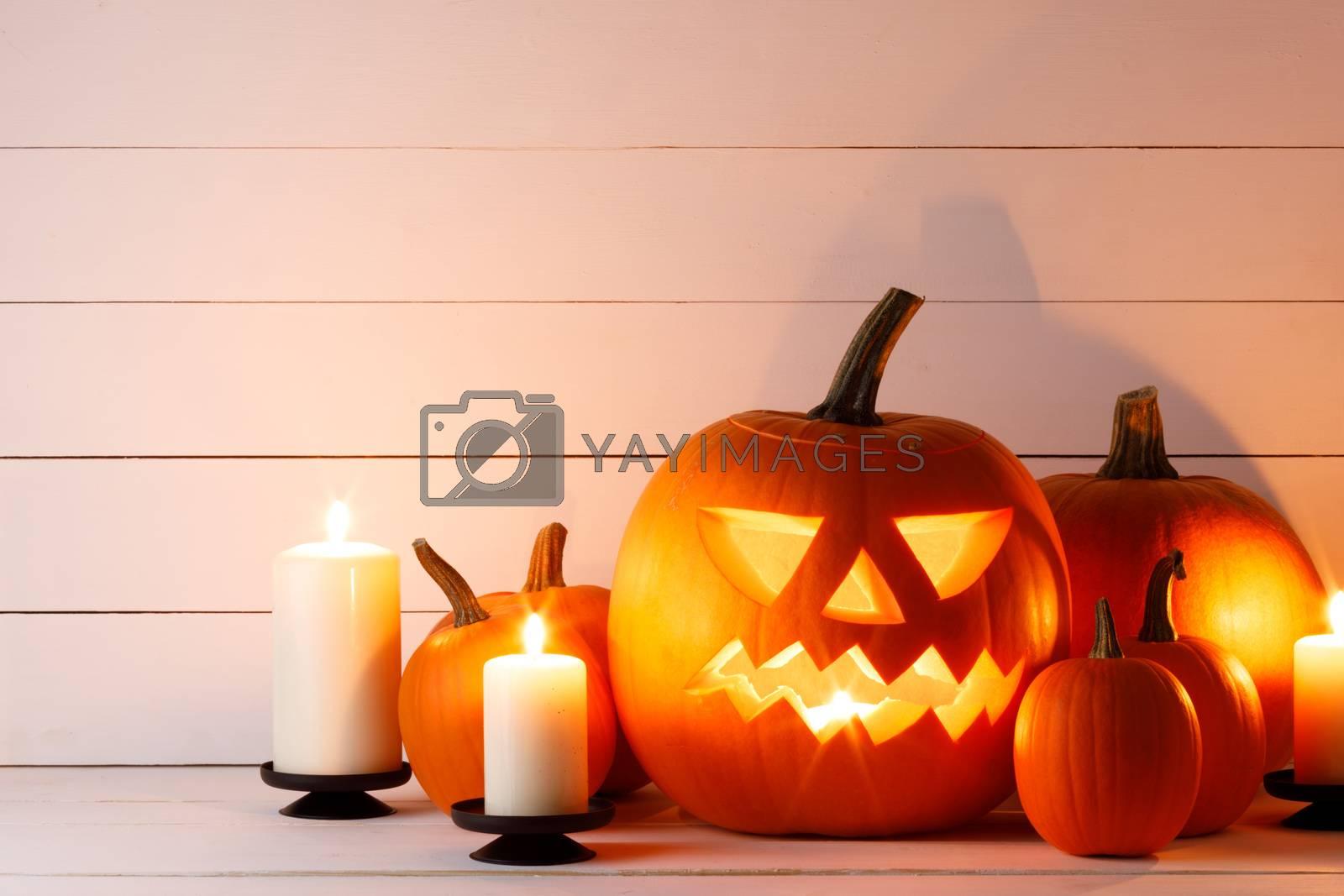 Halloween pumpkin head jack lantern and candles on light wooden background