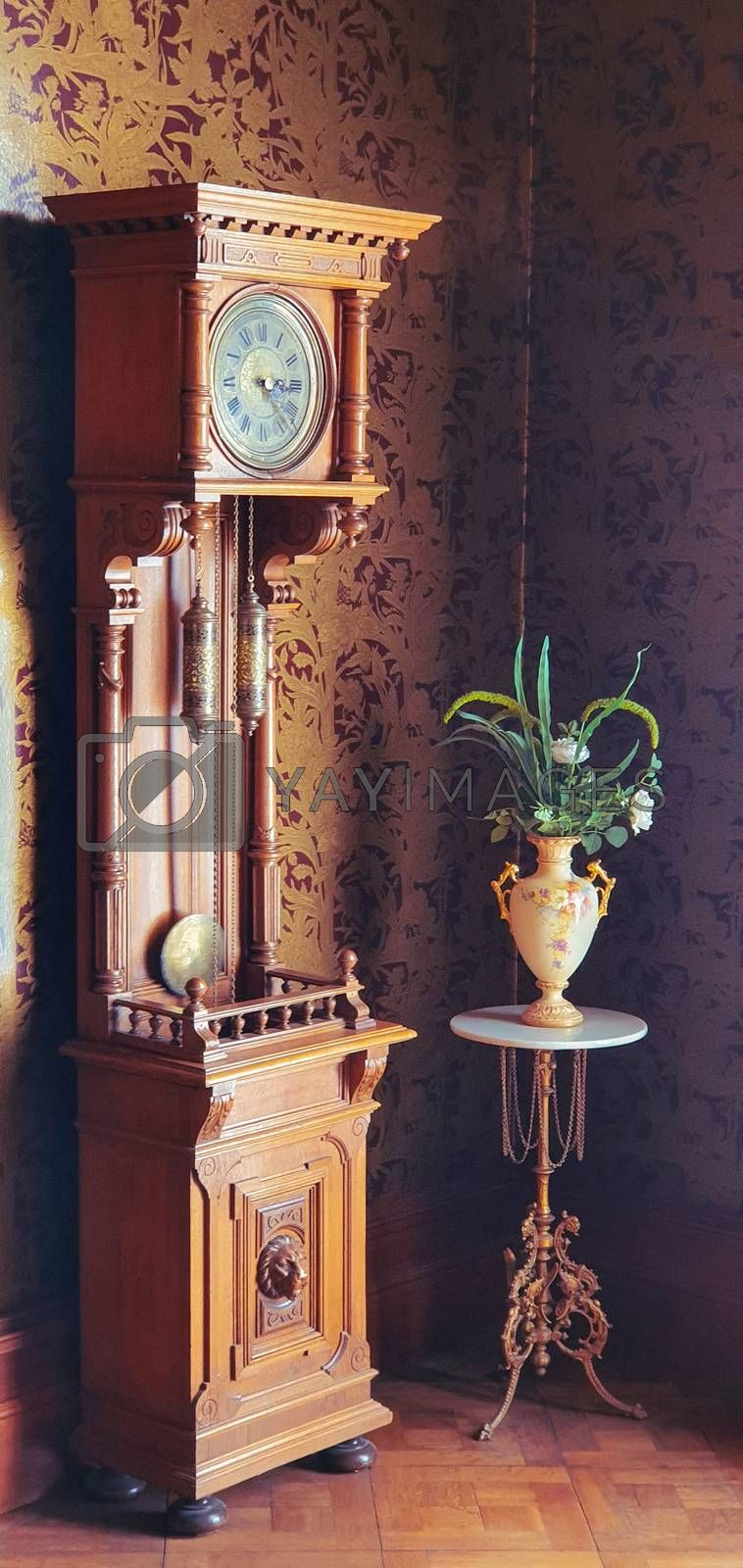 Old fashioned grandfather clock with pendulum and antique vase with flowers in a room with retro designer wallpaper.