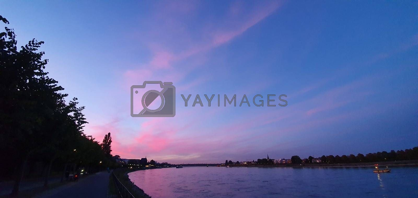 Promenade by the river Rheine in Bonn with a beautiful pink sunset sky.
