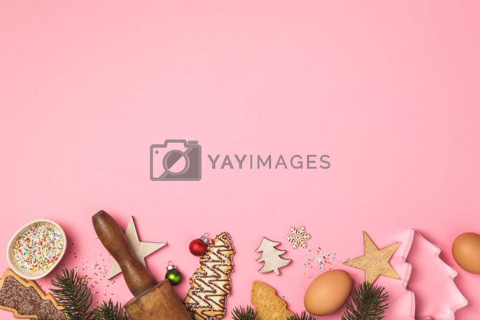Christmas gingerbread cookies in the shape of a Christmas tree and baking ingredients on pink background