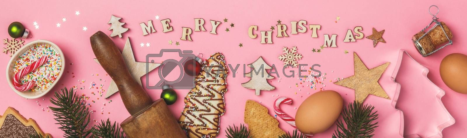 Christmas gingerbread cookies in the shape of a Christmas tree, baking ingredients and Merry Christmas written with wooden letters on pink background