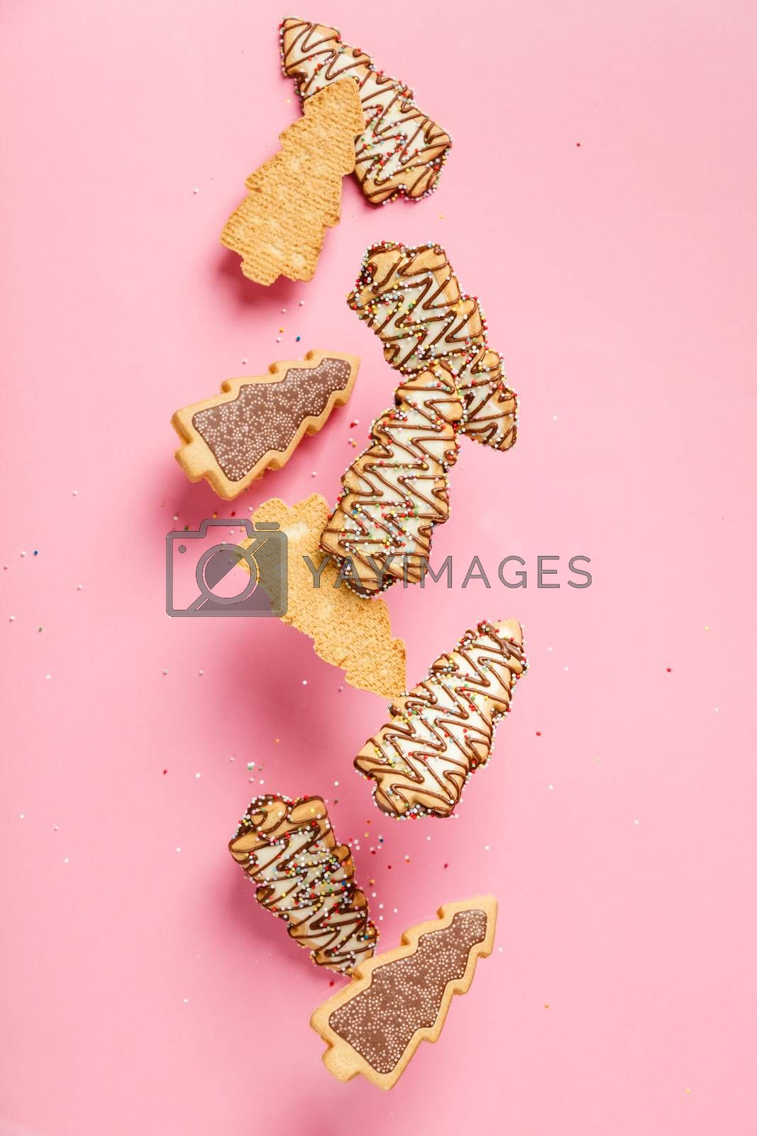 Christmas gingerbread cookies in the shape of a Christmas tree falling or flying in motion against pastel pink background
