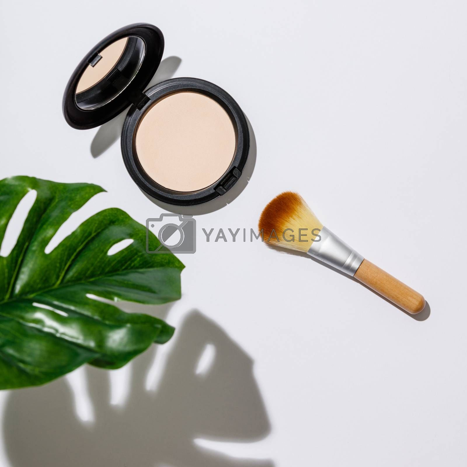 Face powder and brush for makeup and monstera leaves on a white background, flat lay