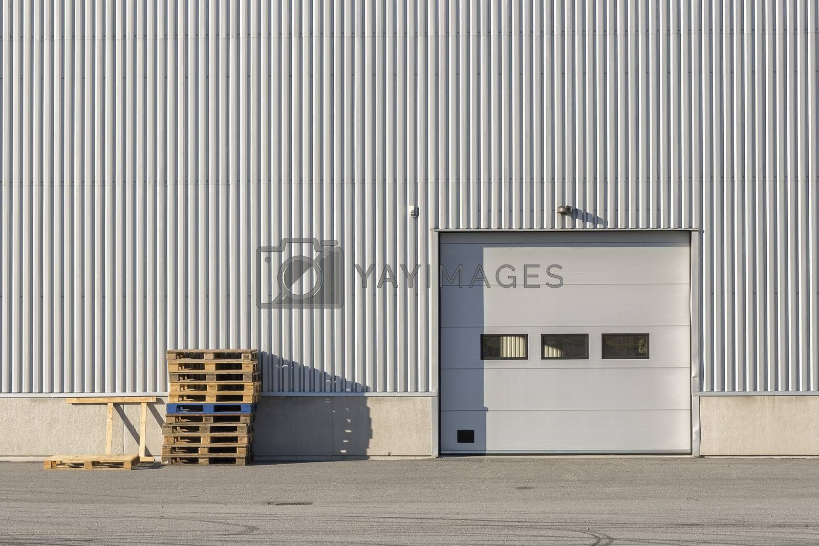 Industrial Building with Garage Door and Box Pallets.