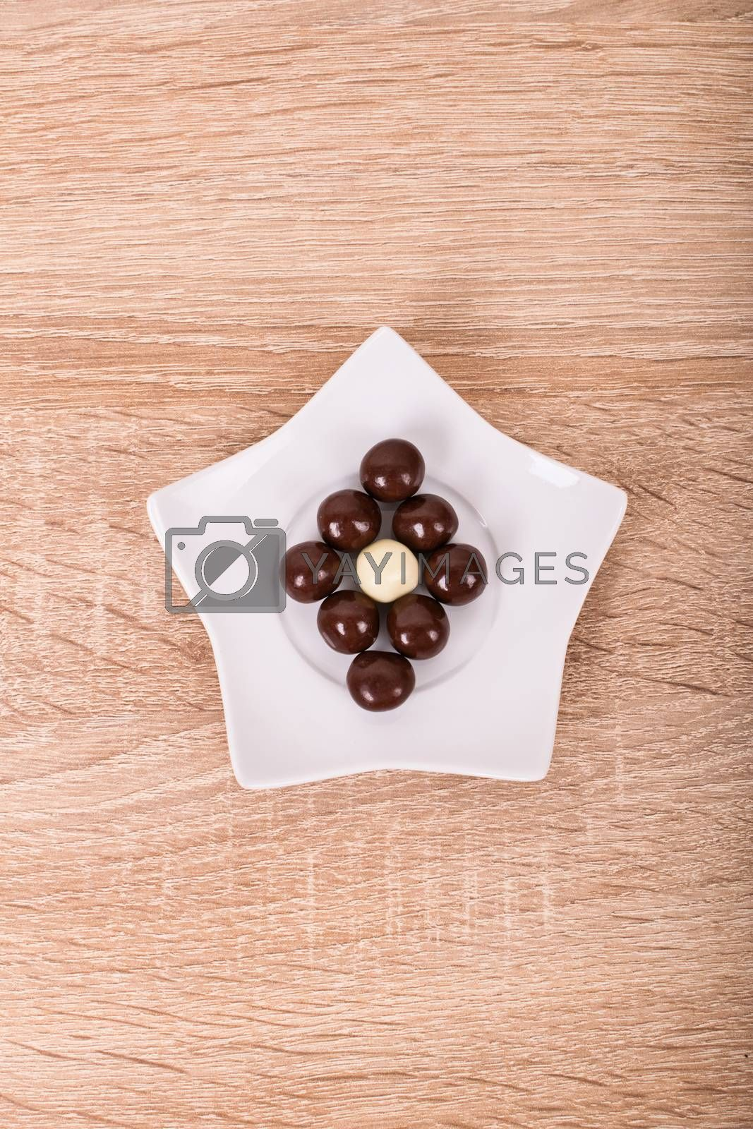 Chocolate balls on a star shaped ceramic white saucer, on a wooden background.