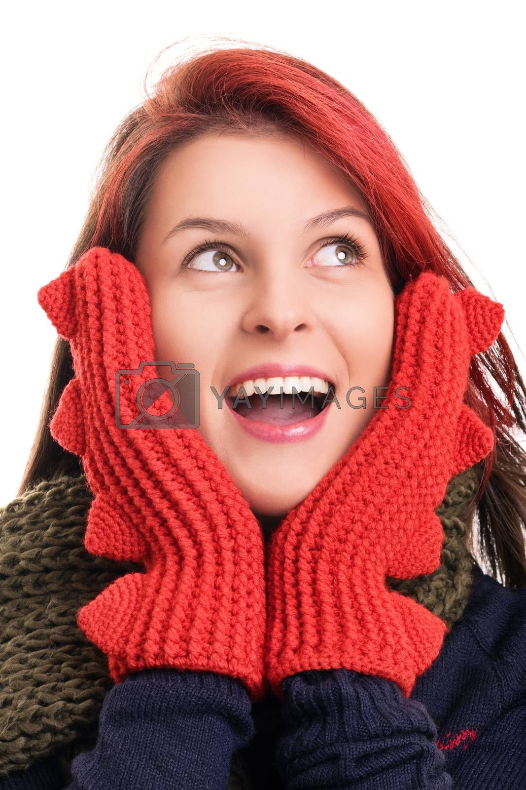 Close up shot of a beautiful surprised young woman with red mittens looking upwards, isolated on white background. Surprised young girl in winter clothes with open mouth holding her face, isolated on white background.