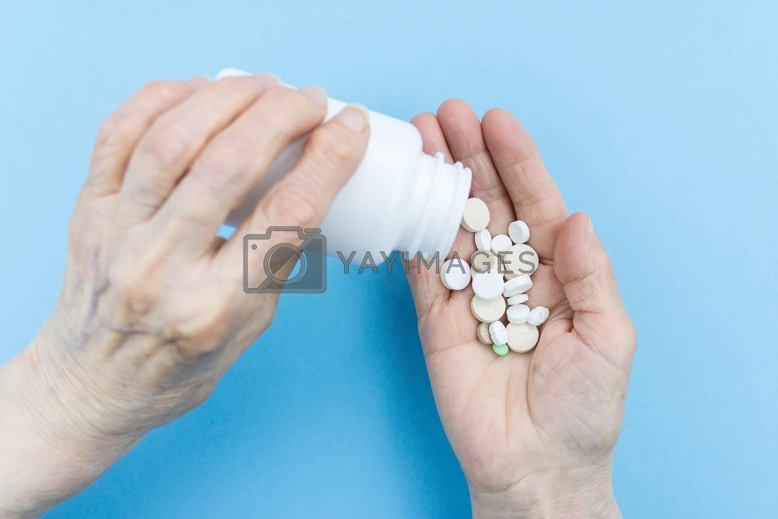Medicine pills or capsules in elder hand.