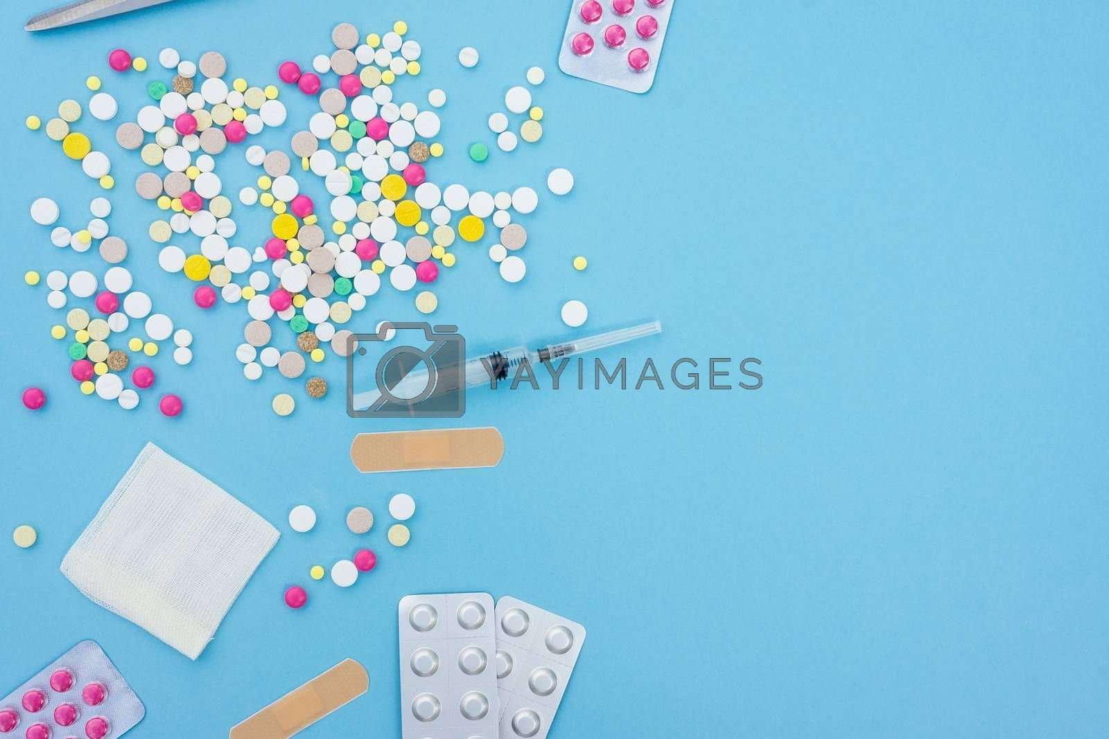 Assorted pharmaceutical medicine pills, tablets and capsules over blue background