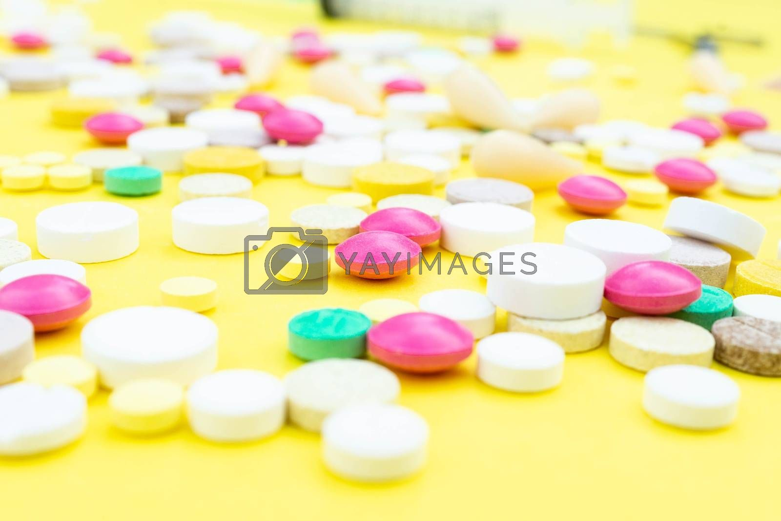 Assorted pharmaceutical medicine pills, tablets and capsules over yellow background