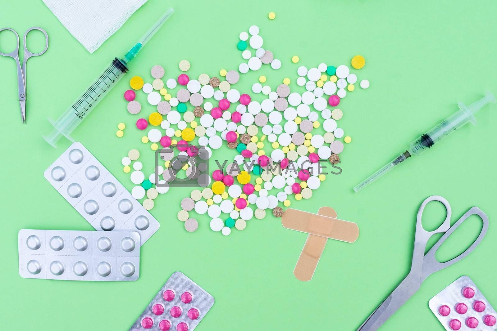 Подпись:Assorted pharmaceutical medicine pills, tablets and capsules over green background
