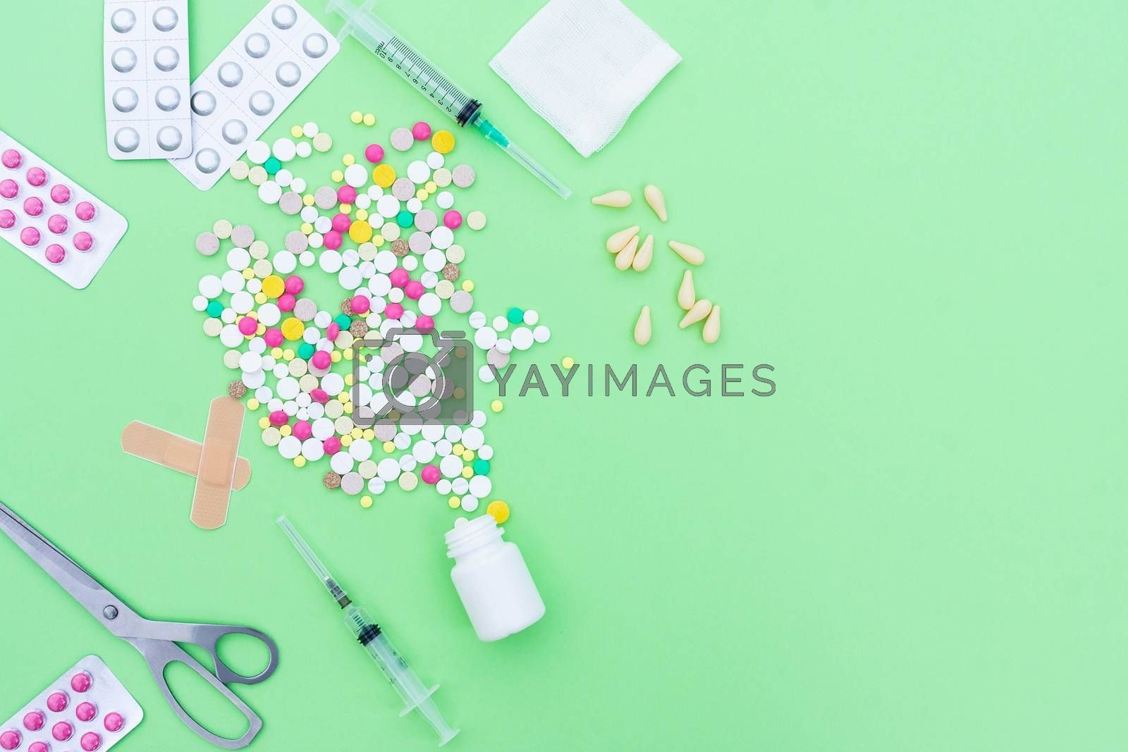 Assorted pharmaceutical medicine pills, tablets and capsules over green background