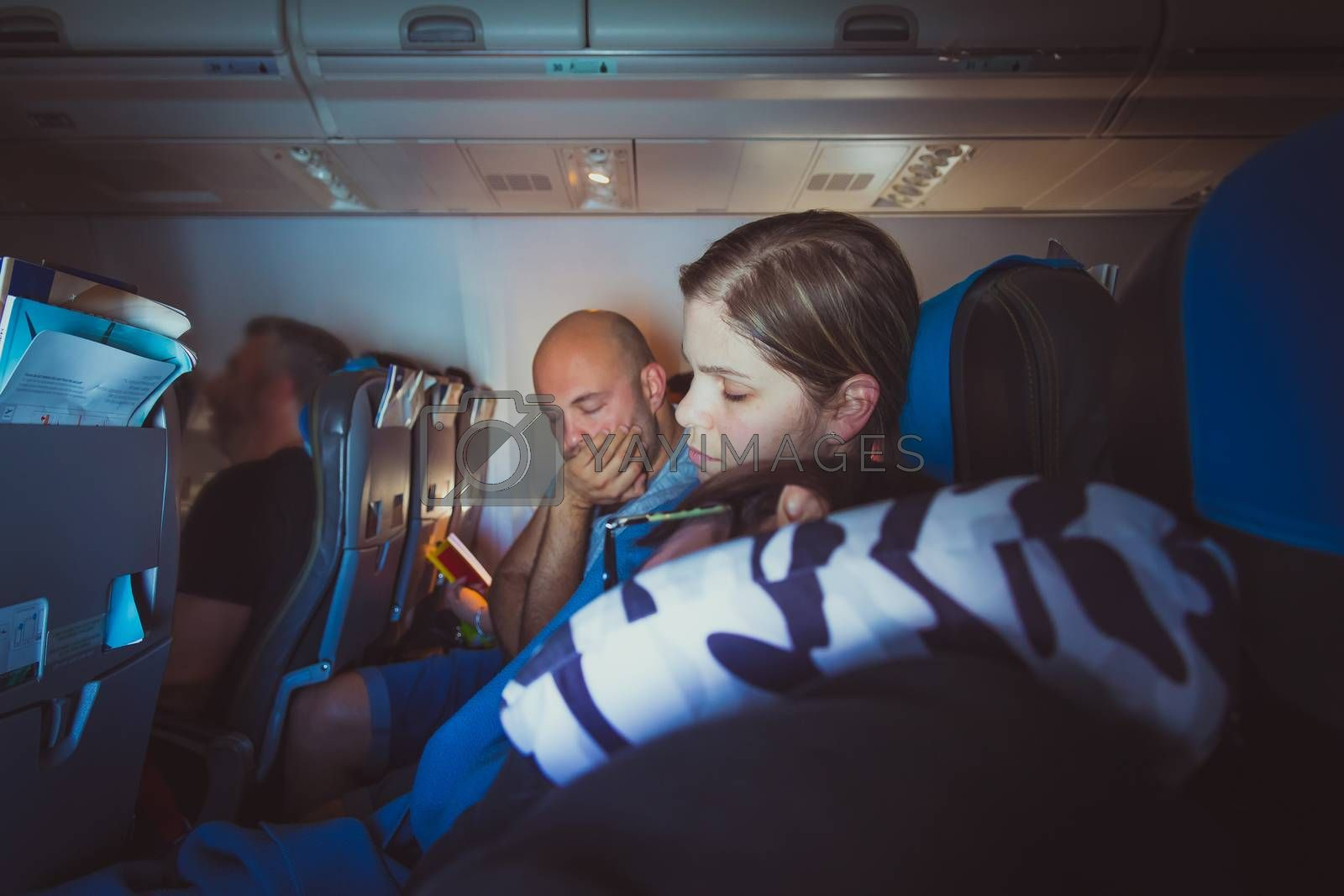 Tired caucasian men and women sleeping on seats while traveling in a commercial airplane.