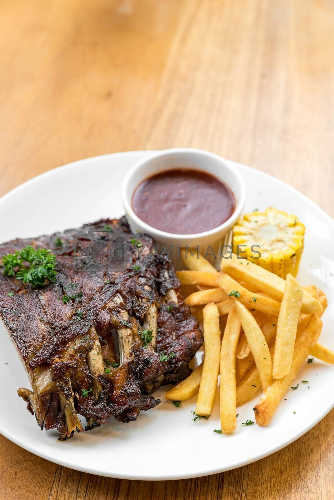 Grilled Barbecued Pork Baby Back Ribs with grilled sweet corn and fries