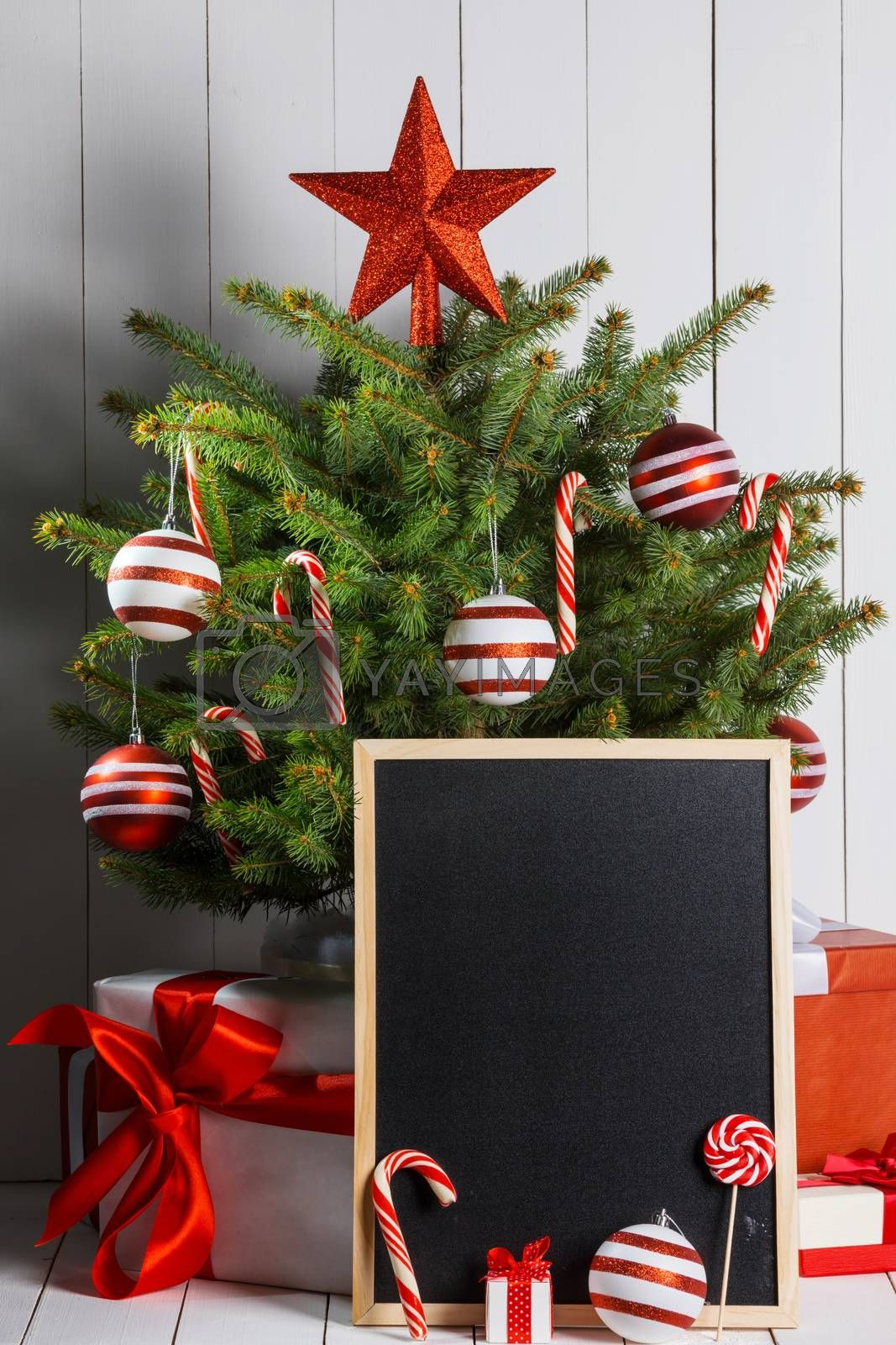 Rustic chalkboard and christmas tree decorated with candy canes and baubles