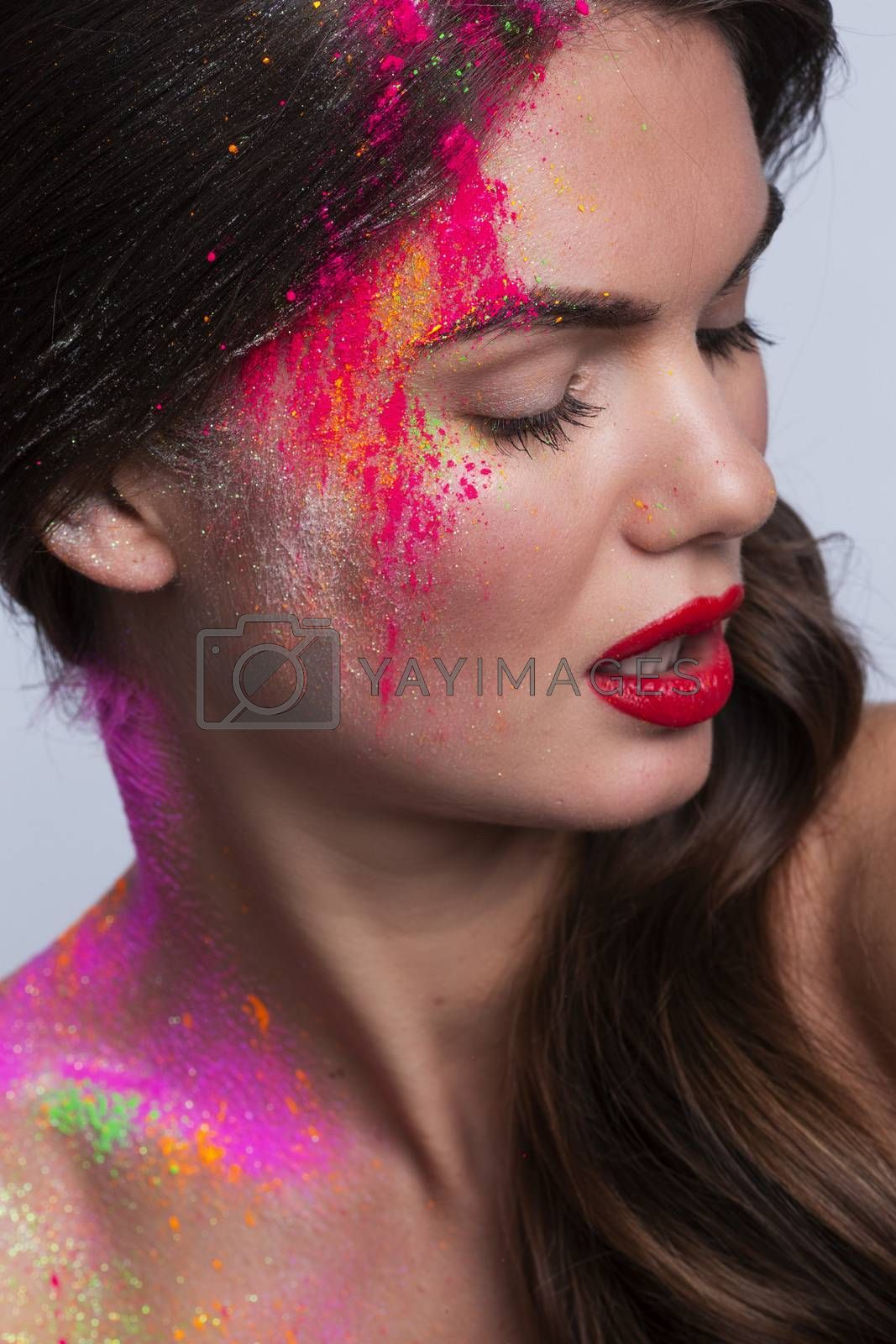 Beautiful woman face with colorful powder makeup closeup