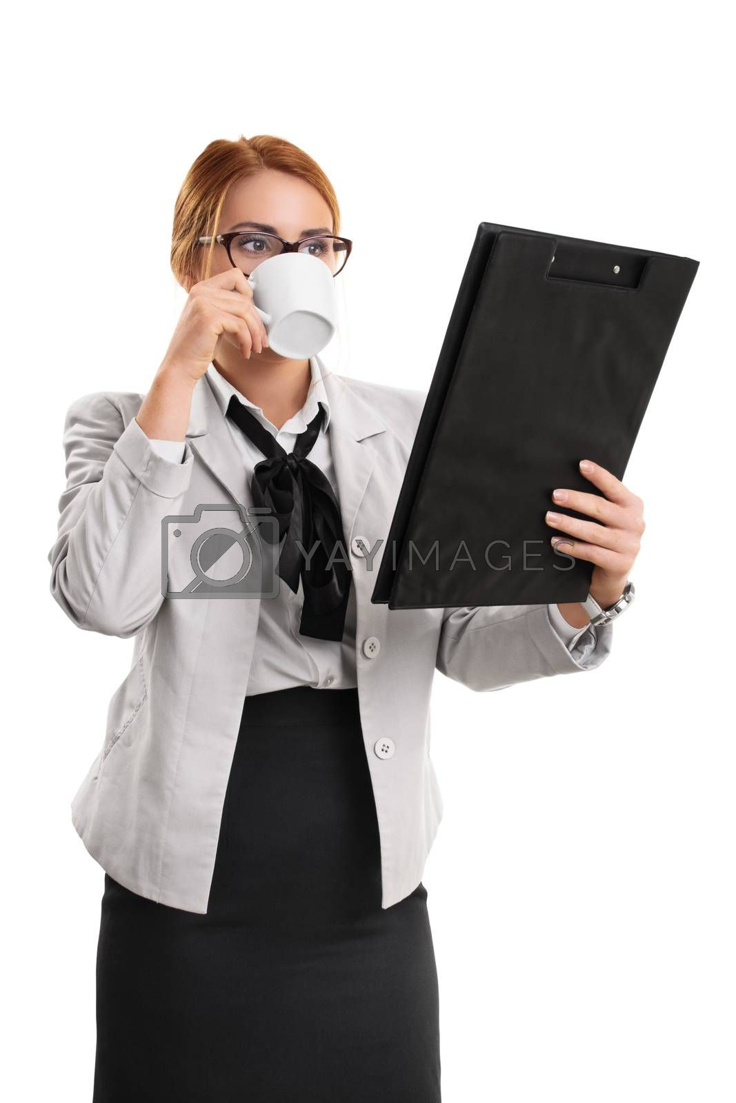 A portrait of a businesswoman drinking from a cup and looking at a clipboard, isolated on white background.