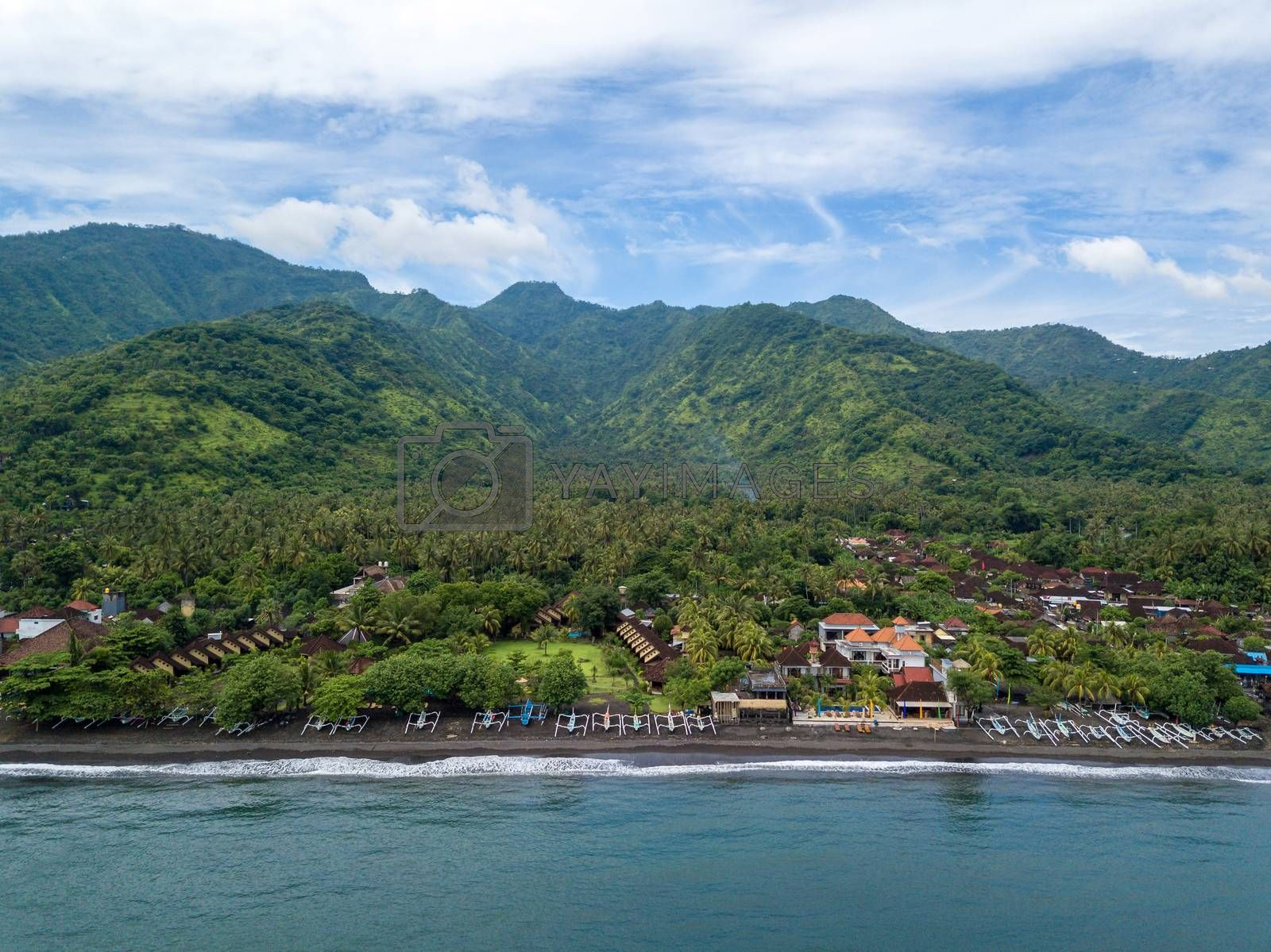 Aerial view of Amed beach in Bali, Indonesia. Traditional fishing boats called jukung on the black sand beach.