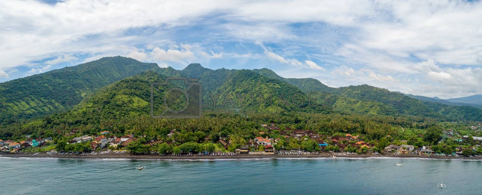 Panoramic aerial view of Amed beach in Bali, Indonesia. Traditional fishing boats called jukung on the black sand beach.