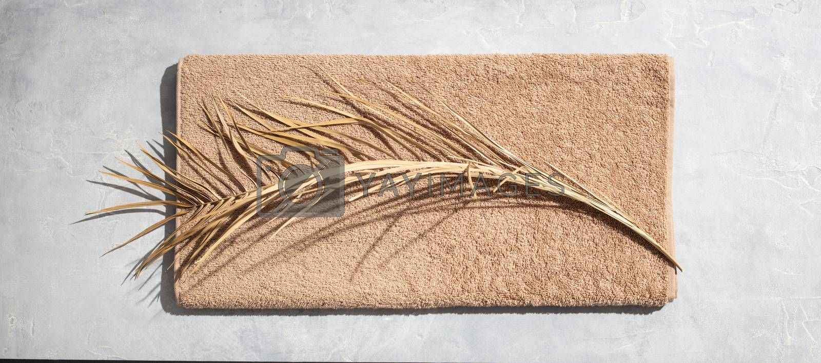 Dried leaf of palm and towel on concrete background, flat lay