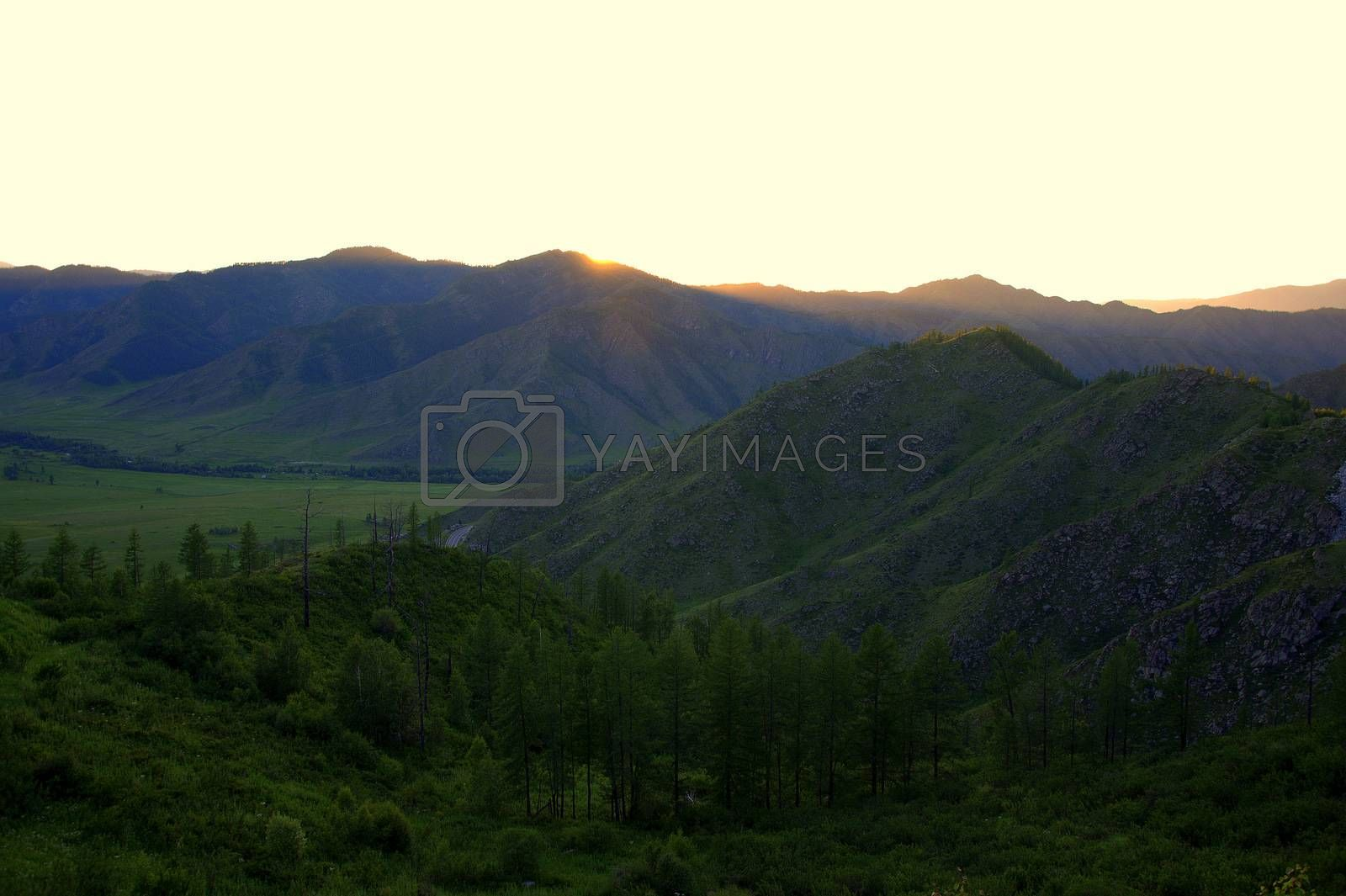 The evening landscape, the setting sun hid behind high mountains, illuminating the picturesque valley with its rays. Altai, Siberia, Russia.