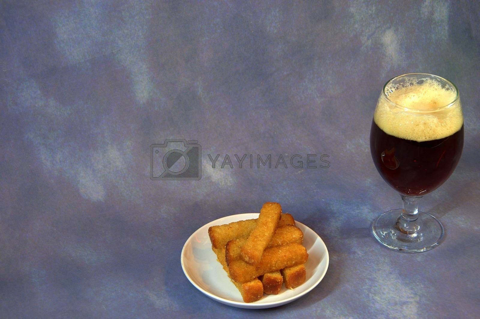 A glass of dark beer with foam and wheat croutons on a plate. Close-up.