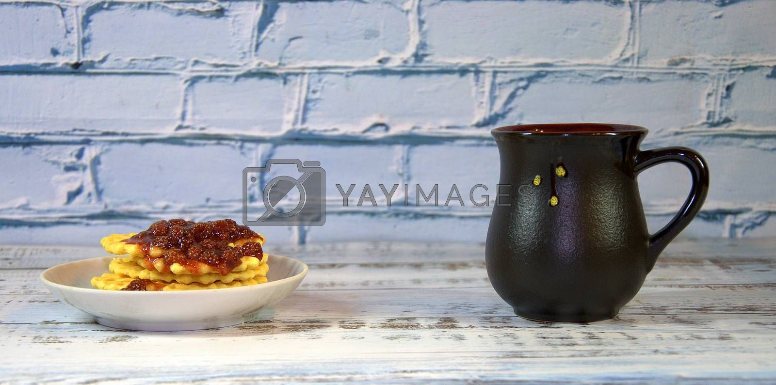 Dark ceramic cup with tea, next to a plate with waffles with strawberry jam. Close-up.