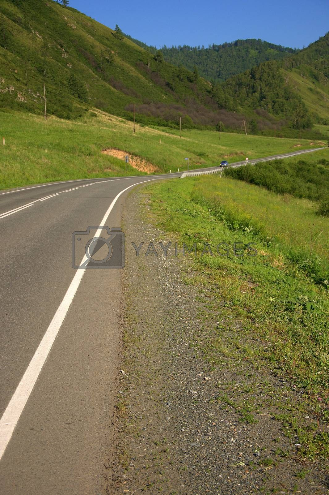 A good asphalt road running through a picturesque valley at the foot of a high hill. Altai, Siberia, Russia.