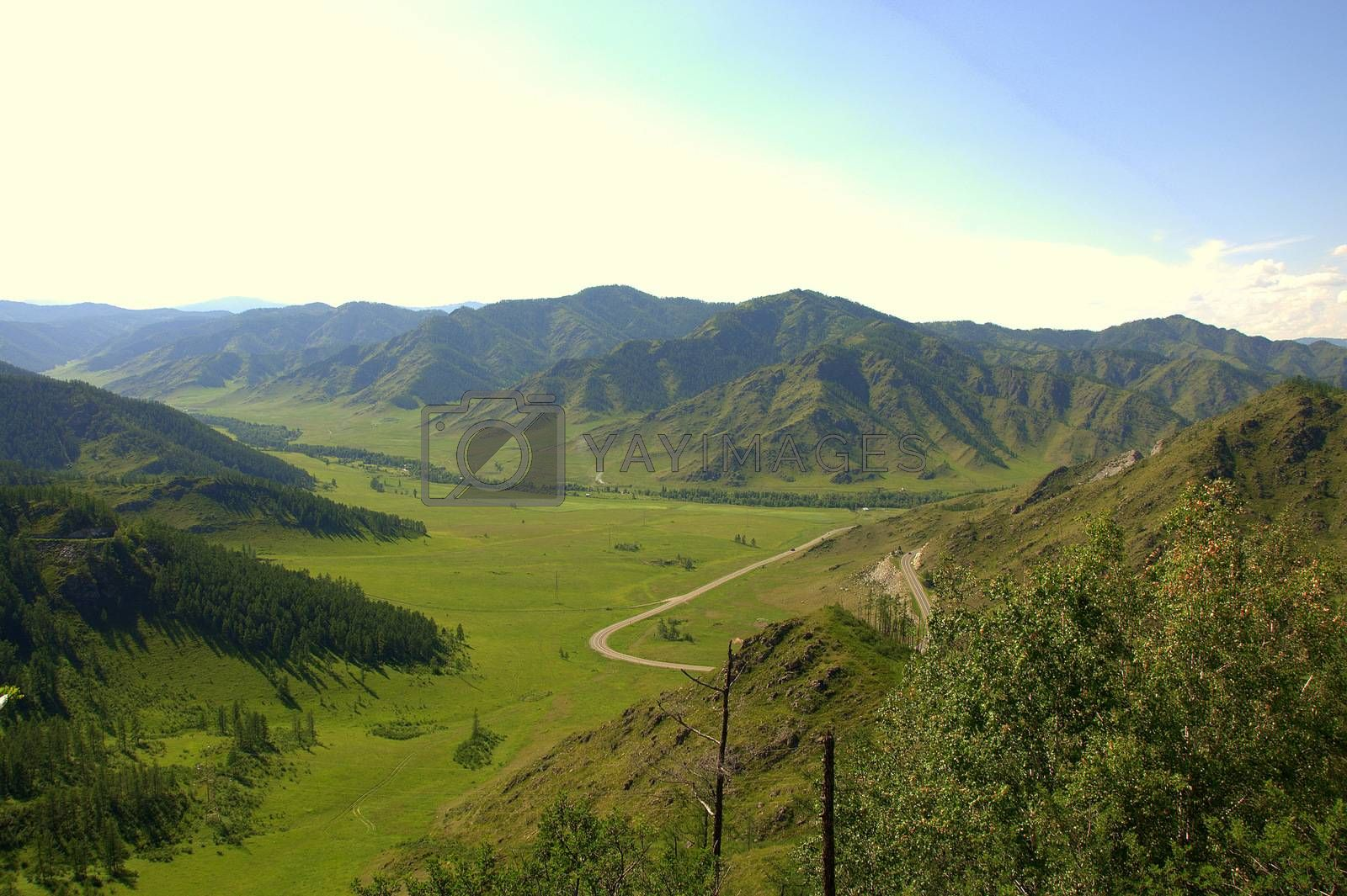 View from the top of the mountain on the road crossing a picturesque valley. Chike-Taman pass, Altai, Siberia, Russia.