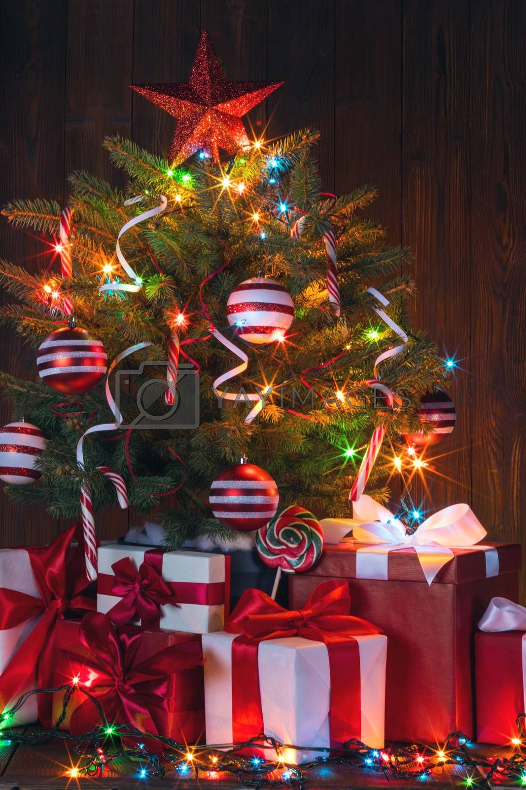Beautiful glowing decorated Christmas Tree and many gifts