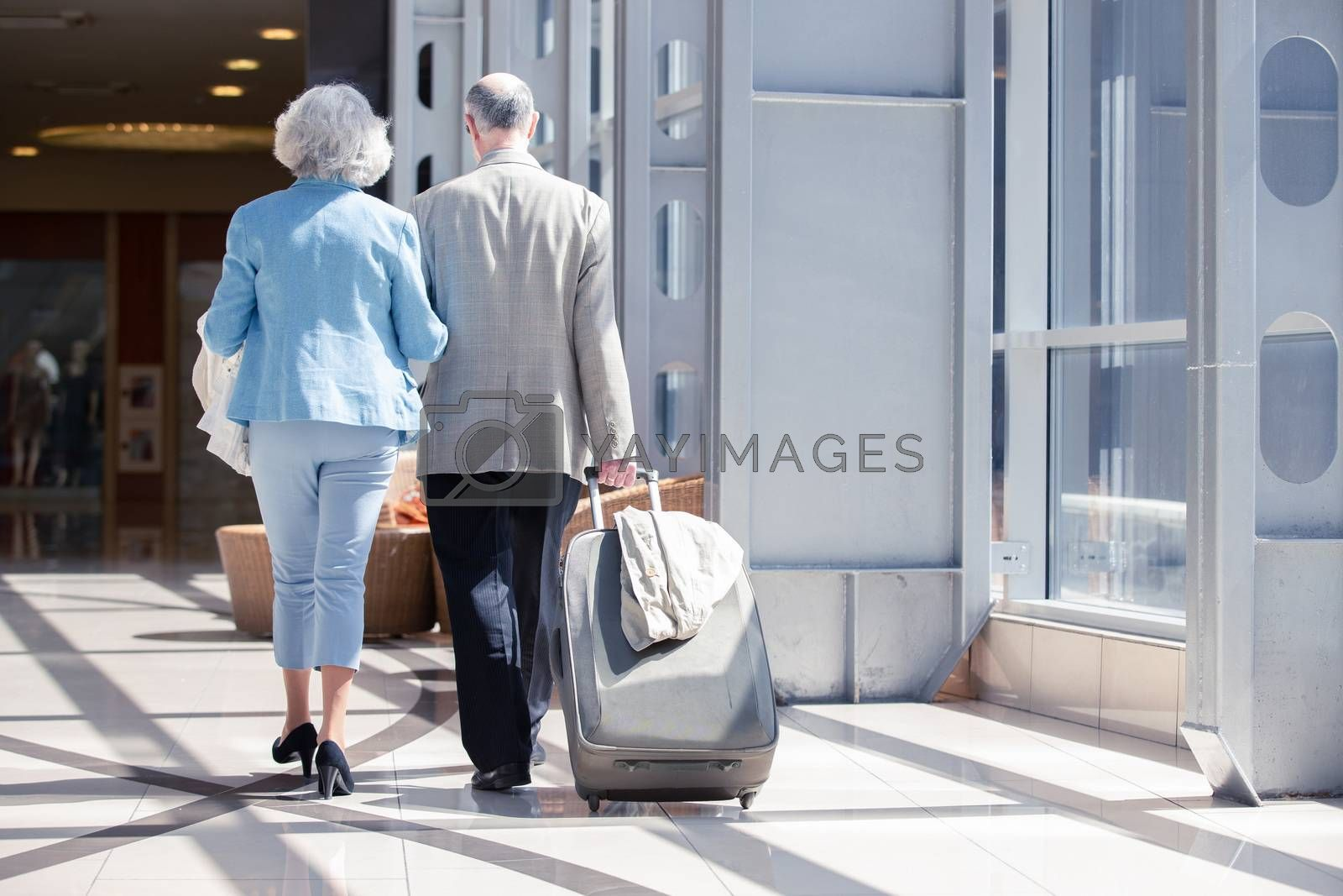 Senior couple in airport walking with suitcase. Holiday travel background.