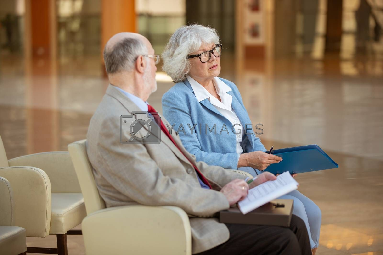 Senior people sitting in lobby and discuss documents
