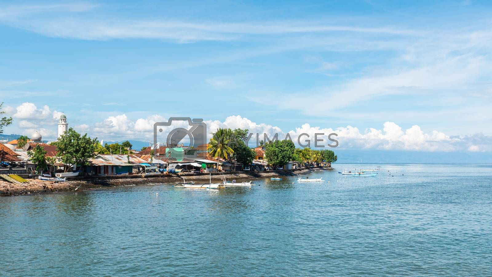 Singaraja in North Bali, Indonesia. Mosque on the left and traditional fishing boats called jukung.