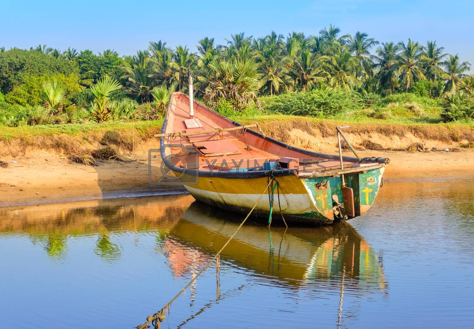 Local colorful fishing boat anchored in the shallow water, copy space