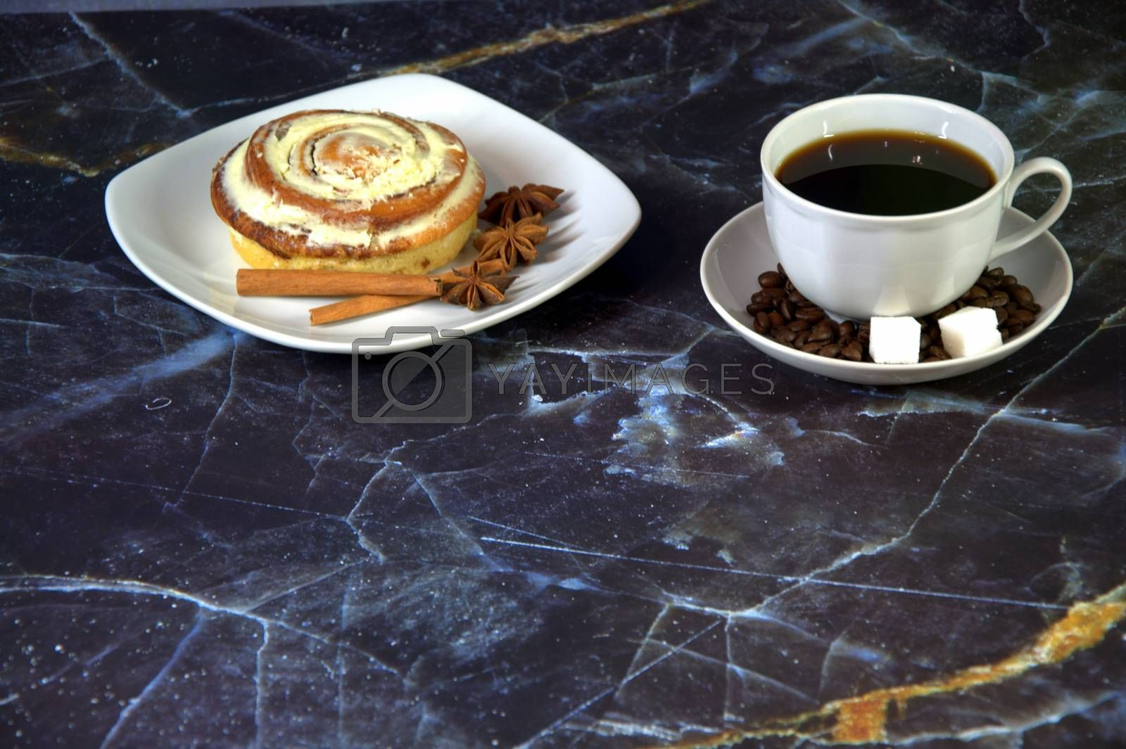 A cup of black coffee with two pieces of sugar in a saucer and a plate with a bun in the glaze with cinnamon sticks and star anise. Close-up.