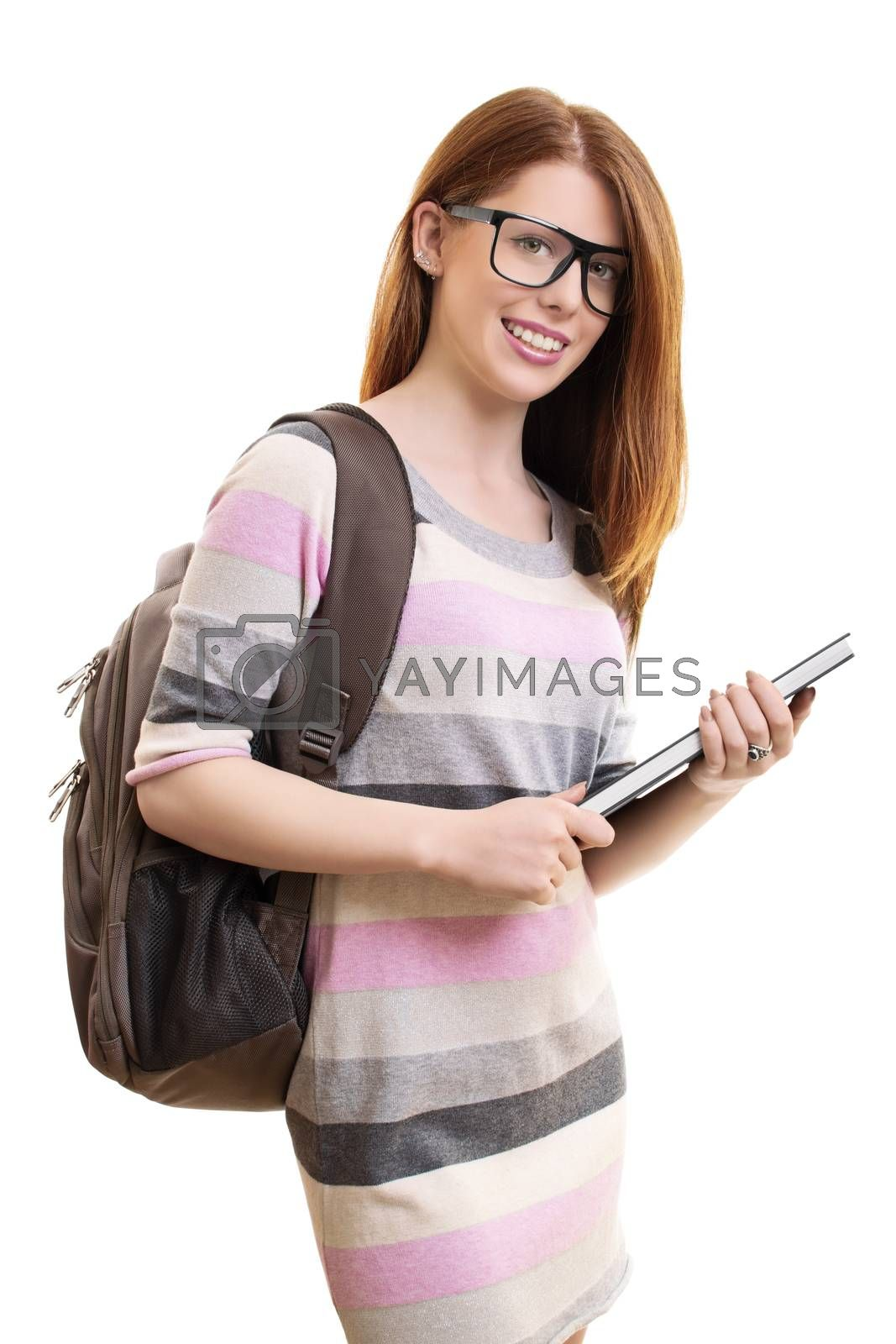 A portrait of a beautiful young female student with glasses and a backpack holding a book, isolated on white background.