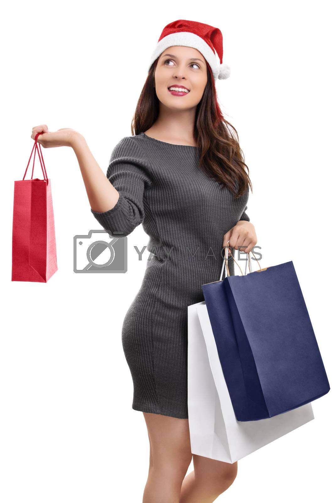 A portrait of a beautiful smiling young girl in winter clothes wearing santa's hat, holding shopping bags, isolated on white background.
