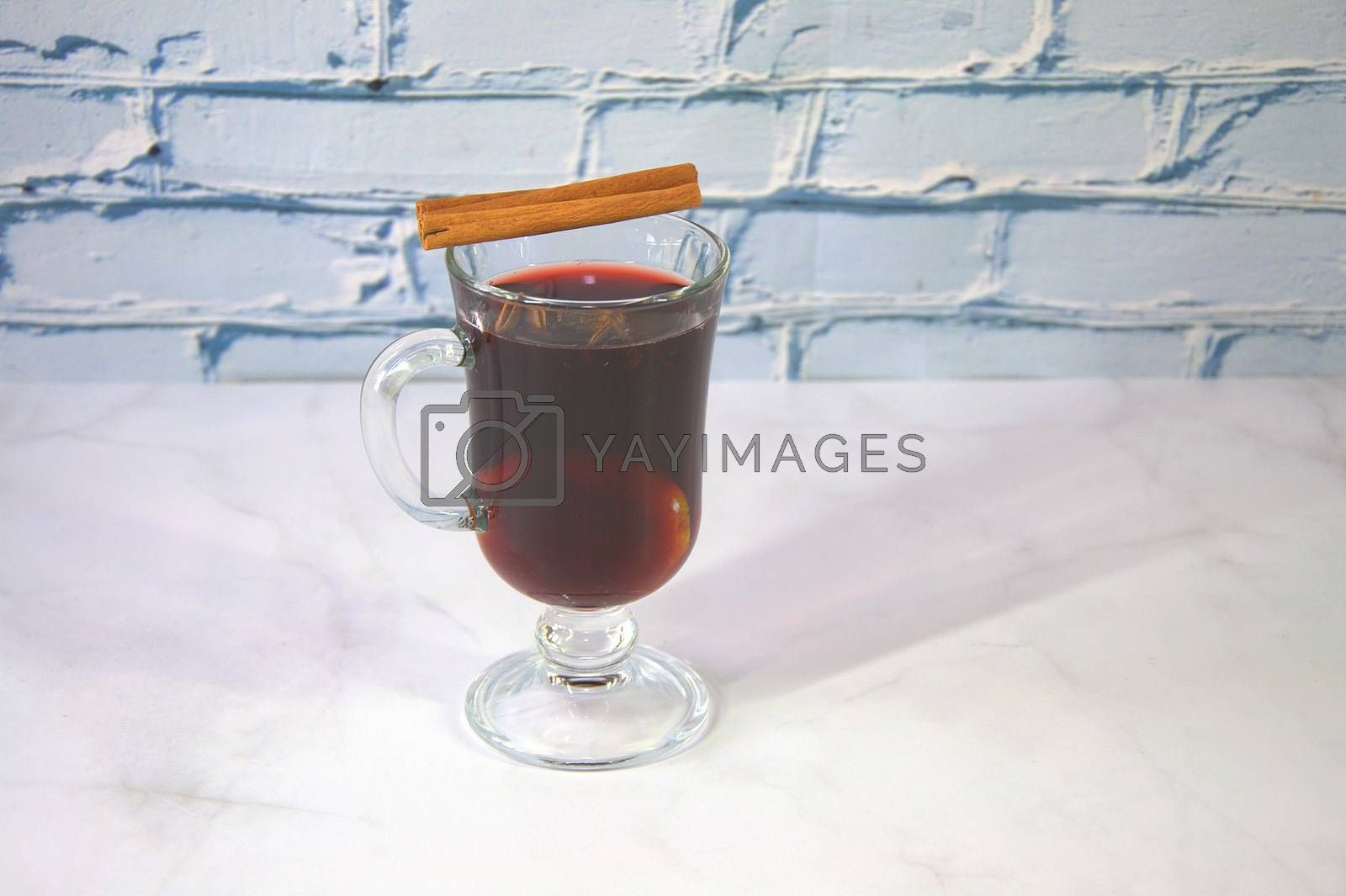 A glass of hot mulled wine with a cinnamon stick on top. Close-up.
